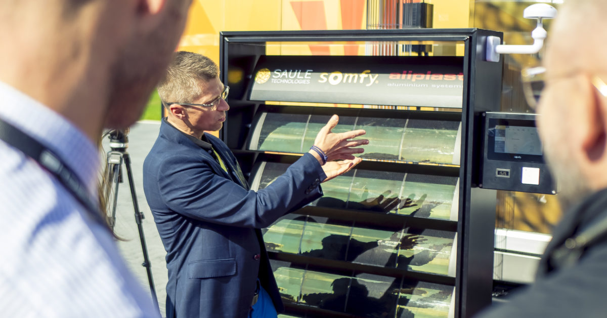 A photograph of the representative from Somfy presenting solar sunblinds demonstrators